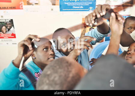 two young teenage Ugandan girls look at a roll of 35mm film during a photography lesson in a rural school - Stock Image