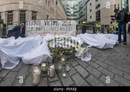 London, UK. 21st December 2018. Climate campaigners from Extinction Rebellion burn candles next to the 'bodies' - mannequins wrapped in white cloth to the BBC representing the bodies of a Greek village killed by fire because of global warming. The protest at the BBC called it to stop ignoring the climate emergency & mass extinctions taking place and promoting destructive high-carbon living through programmes such as Top Gear and those on fashion, travel, makeovers etc. It was organised by the Climate Media Coalition (CMC) and its director Donnachadh McCarth . Peter Marshall/Alamy Live News - Stock Image