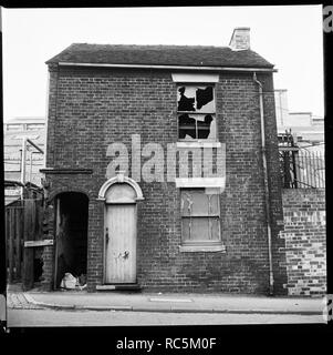 Derelict house, Stoke-on-Trent, Staffordshire, 1965-1968. A derelict house with an industrial complex in the background. This site is unidentified but is likely to be around Middleport, Burslem or Hanley. - Stock Image