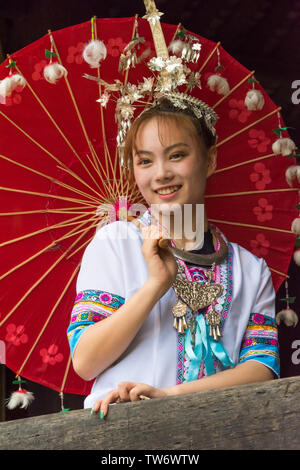 Dong girl in traditional clothing with a red umbrella, Hunan Province, China - Stock Image