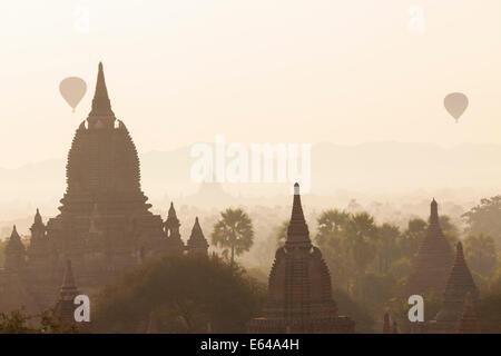 Ancient temple city of Bagan (also Pagan) & balloons at sunrise, Myanmar (Burma) - Stock Image