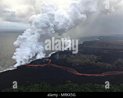 Lava and poisonous sulfur dioxide plumes rise as molten magma reaches the ocean from the eruption of the Kilauea volcano May 24, 2018 in Pahoa, Hawaii. Hot lava entering the ocean creates a dense white plume called 'laze' (short for 'lava haze'). Laze is formed as hot lava boils seawater to dryness. The process leads to a series of chemical reactions that create a billowing white cloud composed of a condensed seawater steam, hydrochloric acid gas, and tiny shards of volcanic glass. The cloud is as corrosive as dilute battery acid, and should be avoided. - Stock Image