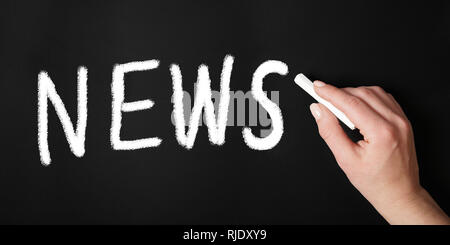 female hand writing the word news with chalk on chalkboard or blackboard - newsletter header - Stock Image
