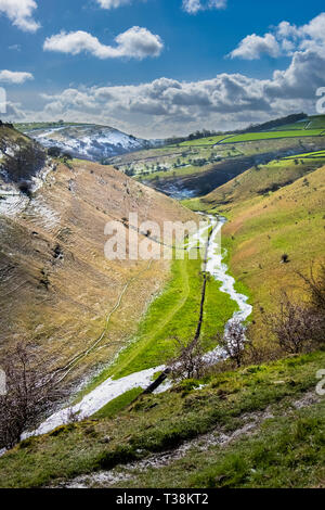 A valley in  Derbyshire which is dry in summer has a stream running through it after a period of rain. - Stock Image