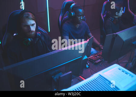 Group of multi-ethnic cybersport players in headsets sitting in front of computers and playing video games online - Stock Image