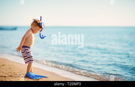 three years old boy playing at the beach with swimming ring - Stock Image