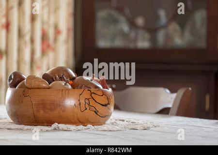 hand turned wooden fruit bowl containing hand turned wooden fruit on table - Stock Image