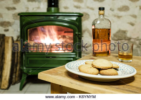 Cookies and Bourbon Whisky left out for Santa Claus in front of a wood-burning fire place. - Stock Image