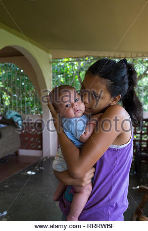 Nicaraguan woman holds her child in a old house in Managua. - Stock Image