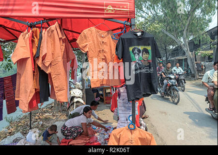 Vendor selling T-shirts of Aung San Suu Kyi and her father Aung San in the Mahaaungmyay district of Mandalay, Myanmar - Stock Image