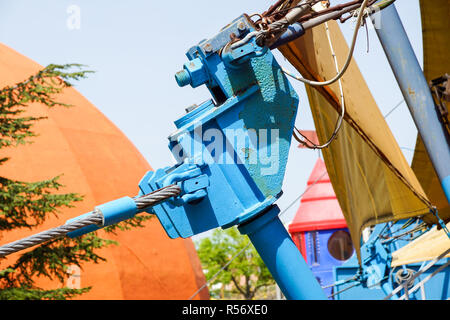 a steel pedestrian bridge tenso structure with support poles and tie-rods on a sunny day with a blue sky - Stock Image