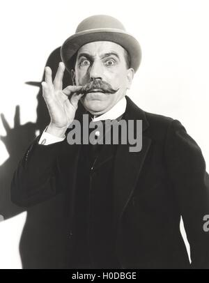 Wide-eyed man touching his mustache - Stock Image