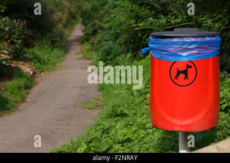 Dog poo bin on footpath. - Stock Image