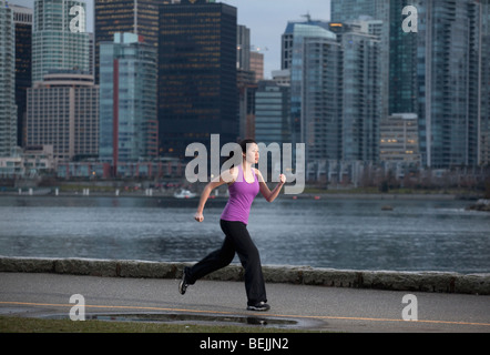 A young Asian woman jogging along the Stanley Park seawall with the city skyline beyond, Vancouver, British Columbia, - Stock Image