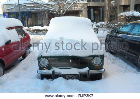 An old Lada car is submerged under recent heavy snowfall in the city of Novi Sad, Vojvodina, Serbia. - Stock Image