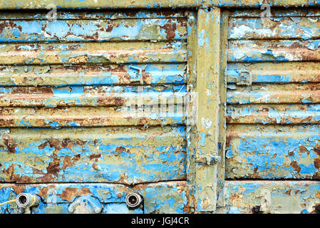 Old corroded blue metal with rust flecks and peeling damaged paintwork - Stock Image