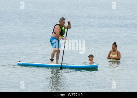 Lyme Regis, Dorset, UK.  13th July 2019. UK Weather.  A man paddleboarding at the seaside resort of Lyme Regis in Dorset on a warm cloudy day.  Picture Credit: Graham Hunt/Alamy Live News - Stock Image