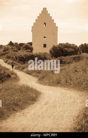 A woman runs by the buried church: A woman jogs by the famous church partially buried in the dune sands near Skagen - Stock Image