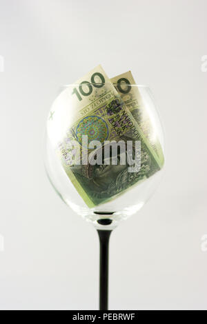 Two banknotes one hundred Polish zlotys inside the wine glass - Stock Image