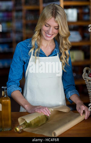 Smiling female staff wrapping olive oil bottle with brown paper - Stock Image