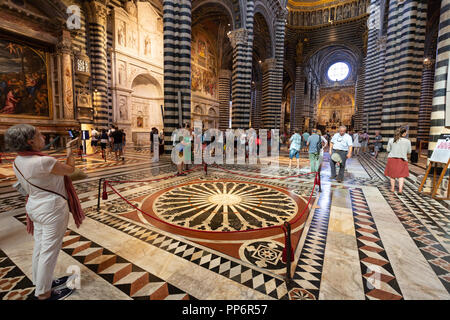 Tourists in the interior of Siena Cathedral ( Duomo Siena ), Siena, Tuscany Italy Europe - Stock Image