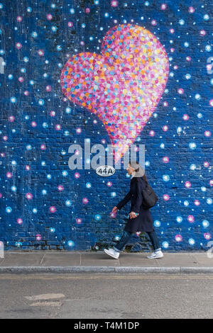 A woman walking along a street next to a wall covered in a painted mural of colourful bubbles and hearts. - Stock Image