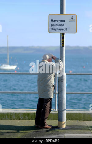 A retired man by the sea looking through binoculars - Stock Image