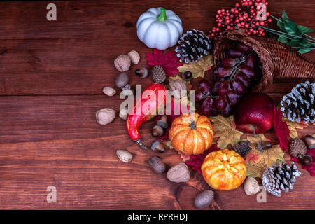 Thanksgiving decor with  frosted pine cones, sunflowers, acorns, pumpkins, grapes, apple, squash, guard, berries and maple leaves - Stock Image