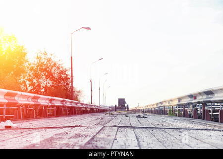 Wooden bridge on the river bank. Wooden road with pillars. Pantone wooden bridge. - Stock Image