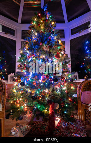 A Christmas tree at night in a house conservatory with presents below, covered in decorations and illuminated by fairy lights, UK - Stock Image