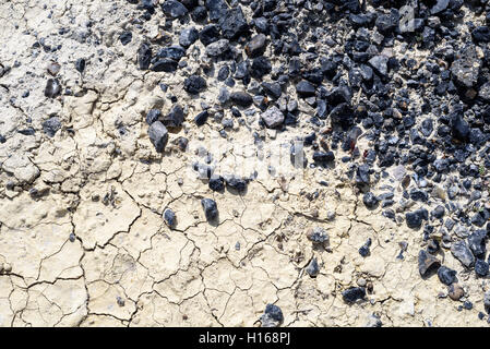 Black tarmac chips merging with a dry cracked mud path in sunshine. Copy space area for construction ideas and concepts. - Stock Image