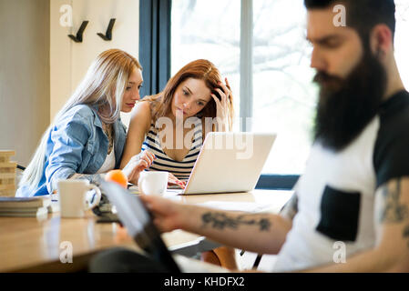Women working together on laptop computer - Stock Image