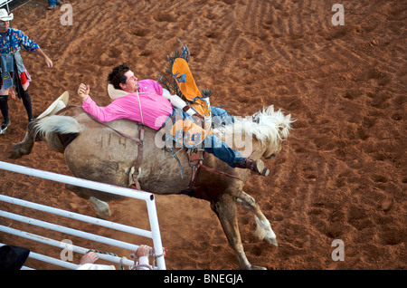 Horse trying to throw rodeo cowboy member of PRCA from its back in Smalltown Bridgeport, Texas - Stock Image