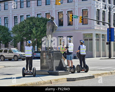 Tourists on a Segway in a tour group stop to view the Hank Williams memorial bronze statue in Montgomery Alabama, USA. - Stock Image