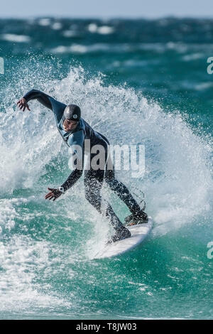 A surfer performs a snap trick on a wave at Fistral in Newquay in Cornwall. - Stock Image