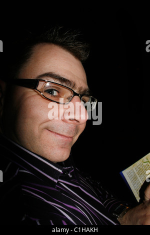 man reading program for play at a theatre - Stock Image