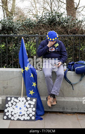 Man with EU flag and beret sat on wall looking at phone, People's Vote March, London, England - Stock Image