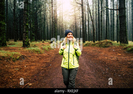 Happy hiker caucasian woman smile and enjoy the nature walking in a forest with high trees - alternative outdoor leisure activity and vacation lifesty - Stock Image