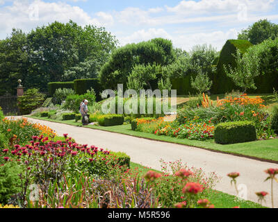 Tourists Flower gardens at the historic medieval grounds and buildings of Penshurst Place. - Stock Image