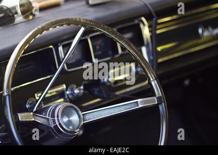Closeup on old classic car steering wheel, interior retro oldtimer - Stock Image