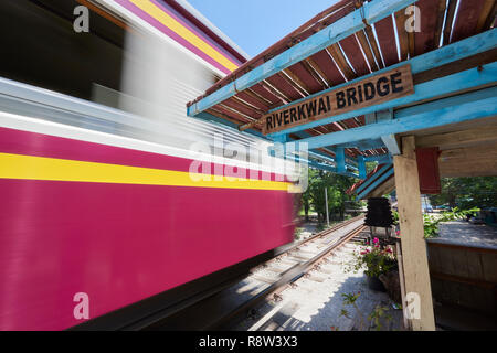 Motion-blurred train whizzes past old waiting gazibo of the Siam-Burma Railway over River Kwai in Kanchanaburi, Thailand. The infamous River Kwai brid - Stock Image