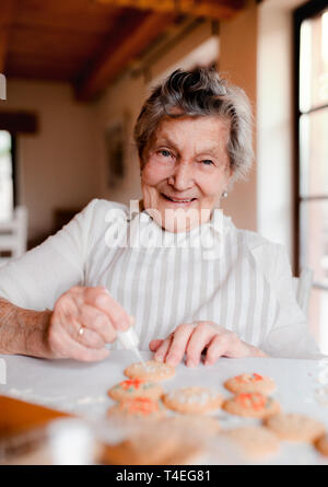 An elderly woman making and decorating cakes in a kitchen at home. - Stock Image