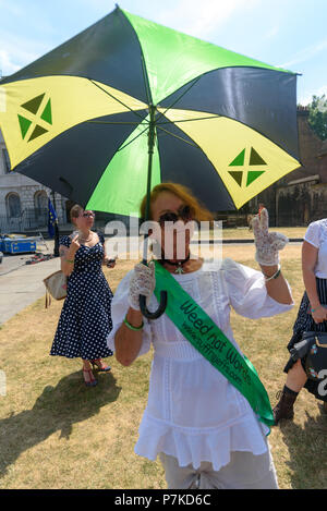 London, UK. 6th July 2018. A woman wears a sash 'Weed not Words,' a play on the suffragette slogajn 'Deeds Not Words' at the protest by members of the group 'We The Undersigned Have a Legal Right to use Cannabis'  in Old Palace Yard in support of Newport West Labour MP Paul Flynn's Private Member's Bill to allow the medical use of cannabis was expected to be debated this afternoon. Objections by MPs prevented the debate and it was pushed back until October. Credit: Peter Marshall/Alamy Live News - Stock Image
