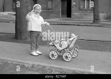 happy young girl waving while pushing a dolls pram 1960s hungary - Stock Image