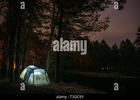 Night landscape with illuminated tent, forest in the background. Summer camping - Stock Image