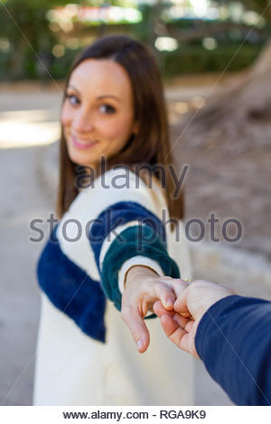 Young girl pulls someone's hand while walking through an urban park - Stock Image