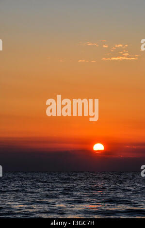 Bright sky and water at colorful sunset over sea landscape - Stock Image