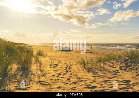 Cyclist rides on the Baltic beach - Stock Image