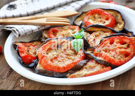 Delicious vegetarian pizza topping, roasted aubergine with tomatoes and basil on the plate on the wooden table - Stock Image