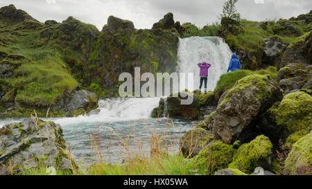 Couple standing on mossy boulders admiring waterfall river in rocky remote landscape - Stock Image
